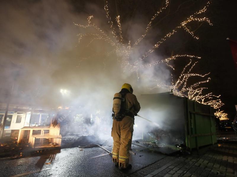Krawalle inRotterdam:Ein Feuerwehrmann löscht einen Container, der bei Protesten gegen die landesweite Ausgangssperre in Brand gesetzt wurde. Foto: Peter Dejong/AP/dpa (© Peter Dejong)