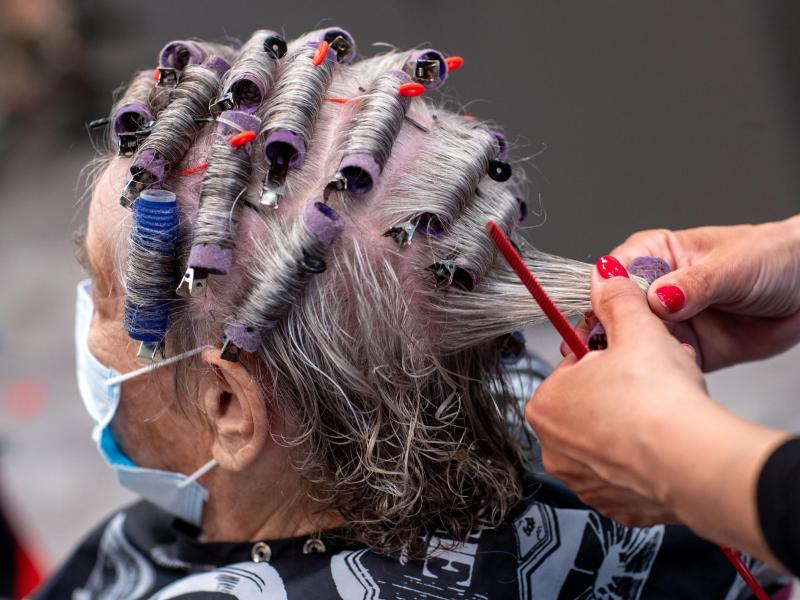Eine Kundin trägt im Frühjahr 2020 Mundschutz in einem Friseursalon. Vielen Betrieben droht im anhaltenden Corona-Lockdown das Aus. Foto: Jens Büttner/dpa-Zentralbild/dpa (© Jens Büttner)