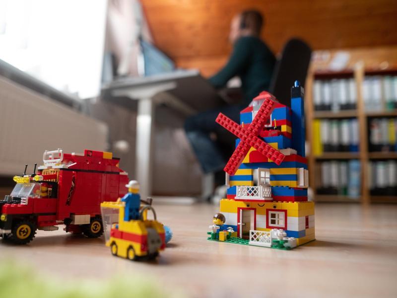 Ein Mann arbeitet im Homeoffice, während im Vordergrund Spielzeug seiner Kinder steht. Foto: Sebastian Gollnow/dpa (© Sebastian Gollnow)