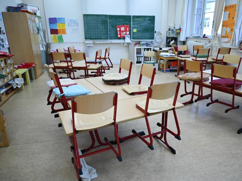 Stühle sind in einem leeren Klassenzimmer in einer Schule in Frankfrut auf den Tischen abgestellt. Foto: Arne Dedert/dpa (© Arne Dedert)