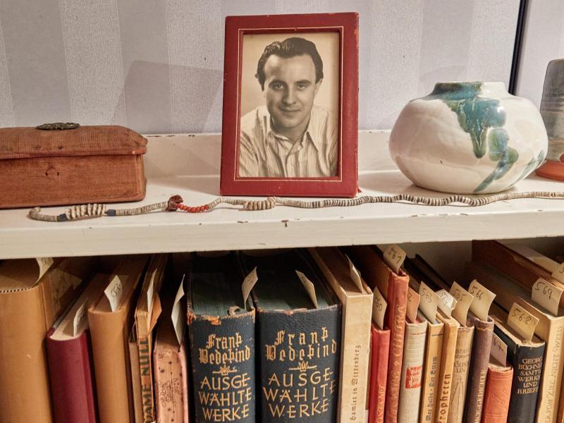 Ein Bilderrahmen mit einem Foto des Schriftstellers Wolfgang Borchert steht auf einem Bücherregal in der «Borchert-Box». Am 20. Mai wäre Borchert 100 Jahre alt geworden. Foto: Georg Wendt/dpa (© Georg Wendt)