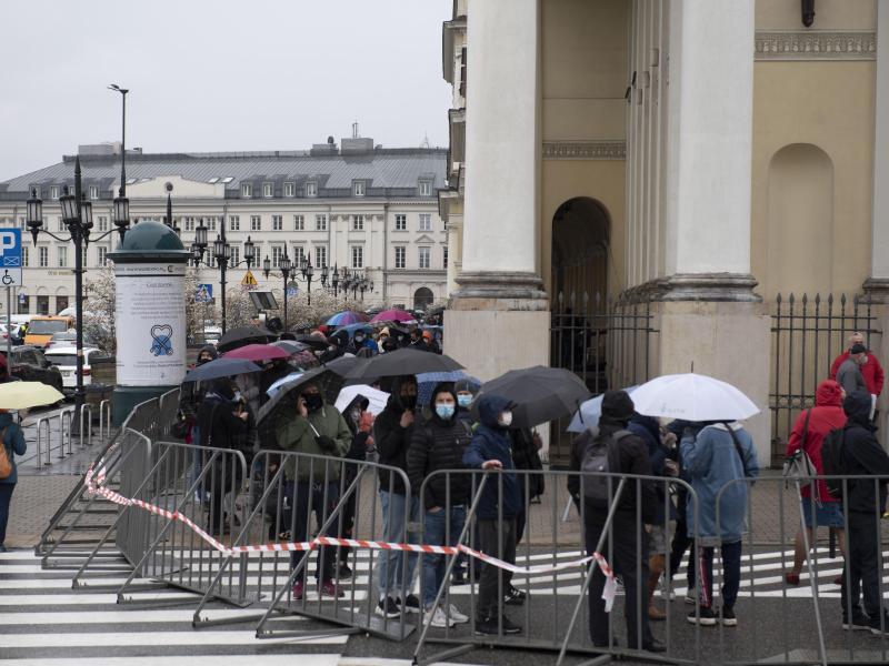 Menschen warten in einer Schlange vor dem Warschauer Rathaus auf ihre Impfung. Foto: Aleksander Kalka/ZUMA Wire/dpa (© Aleksander Kalka)