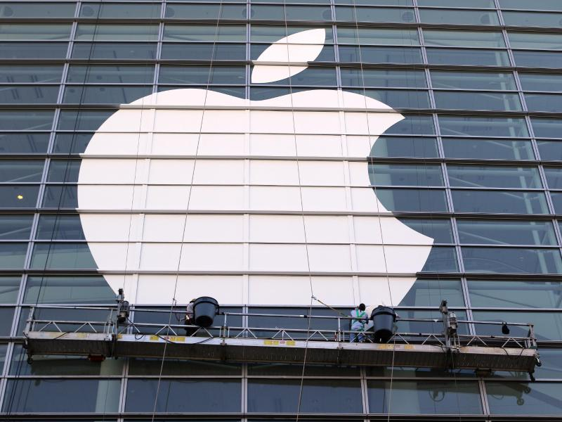 Arbeiter bringen ein übergroßes Apple-Logo an einer Glasfassade in San Francisco an. Foto: Christoph Dernbach/dpa (© Christoph Dernbach)