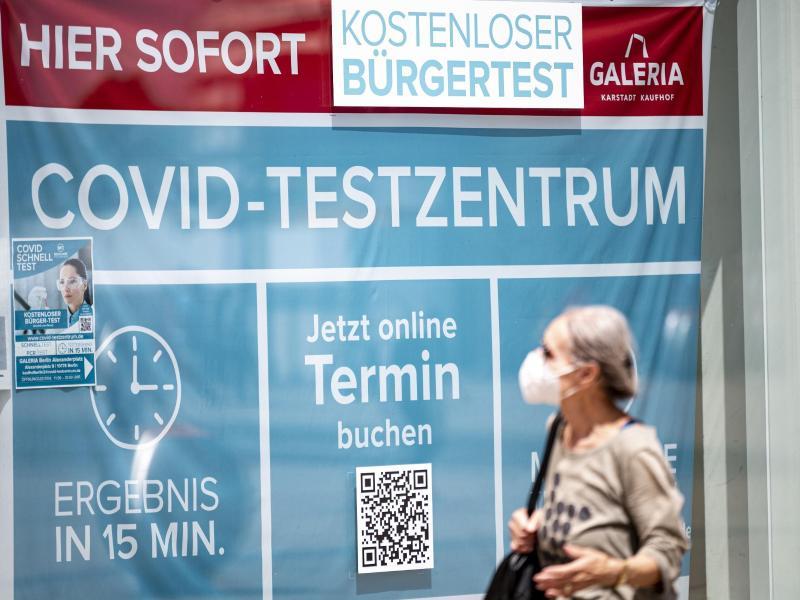 Eine Frau mit Maske läuft an einem Corona-Testzentrum am Berliner Alexanderplatz vorbei. Foto: Fabian Sommer/dpa (© Fabian Sommer)