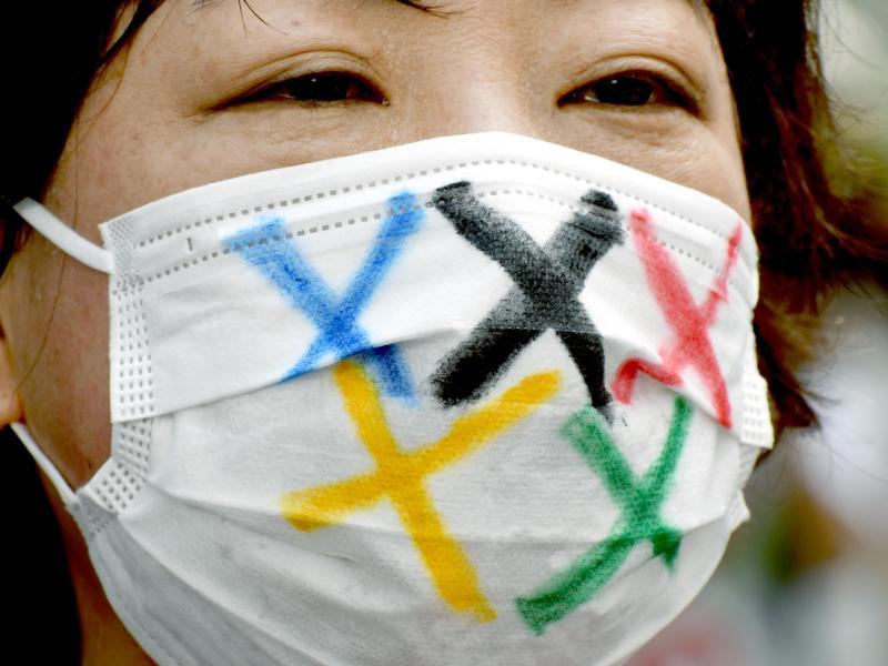 Eine Frau trägt einen Mund-Nasen-Schutz mit den fünf Farben der fünf olympischen Ringe während der Ankunft der olympischen Fackel in Tokio. Foto: Ramiro Agustin Vargas Tabares/ZUMA Press Wire/dpa (© Ramiro Agustin Vargas Tabares)