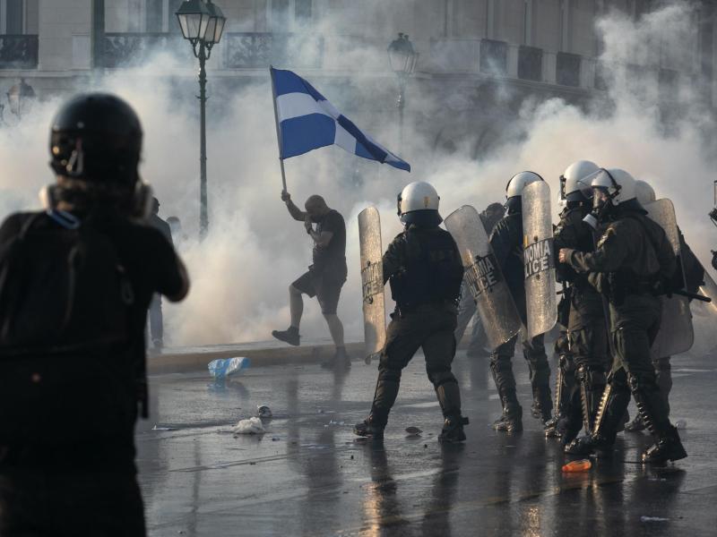 Die griechische Polizei setzt in Athen Tränengas und Wasserwerfer gegen impfkritische Demonstranten ein. Foto: Yorgos Karahalis/AP/dpa (© Yorgos Karahalis)