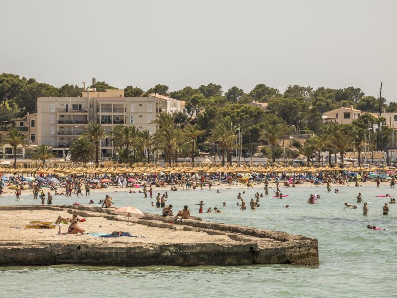 Badegäste am Strand von S'Arenal. Seit Ende Juni sind die Corona-Zahlen praktisch überall in Spanien rapide in die Höhe geschossen. Auf Mallorca lag die Sieben-Tage-Inzidenz zuletzt bei 365. Foto: John-Patrick Morarescu/ZUMA Press Wire/dpa (© John-Patrick Morarescu)