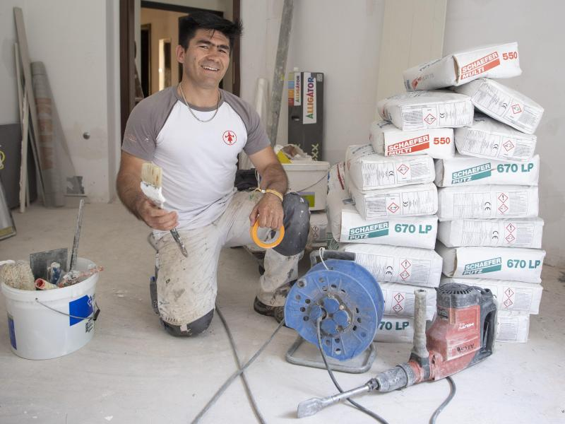 Der aus Afghanistan geflohene Najibullah Alizadah arbeitet auf einer Baustelle auf dem Gelände der Universität. Der aus der Nähe von Kabul stammende Mann absolvierte eine Maler-Ausbildung bei einem mittelständischen deutschen Betrieb. Foto: Boris Roessler/dpa (© Boris Roessler)