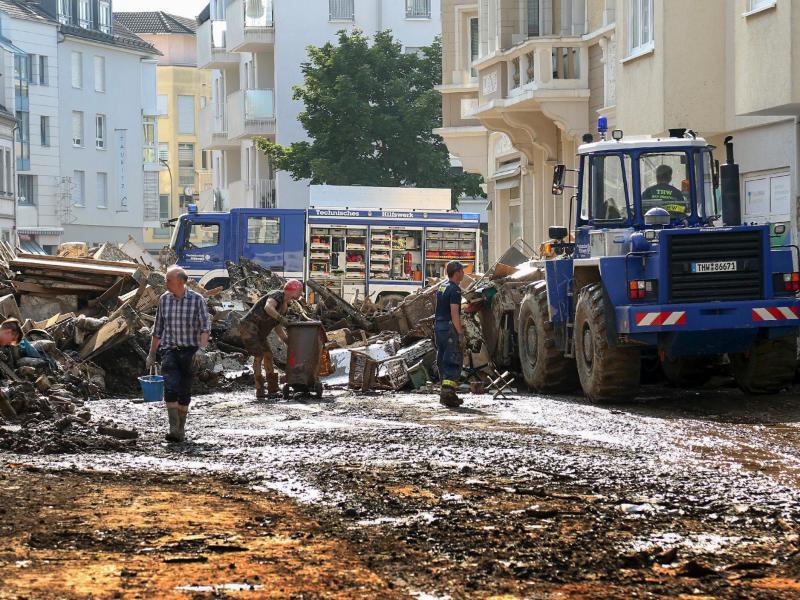 Mitarbeiter des Technischen Hilfswerks (THW) helfen bei Aufräumarbeiten nach der Unwetterkatastrophe in einer verschlammten Straße. Foto: Alexander Mann/THW/dpa (© Alexander Mann)