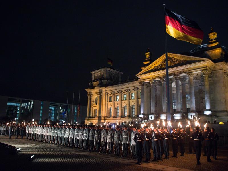 Zahlreiche Soldaten stehen bei einem Großen Zapfenstreich vor dem Reichstagsgebäude in Berlin. Foto: picture alliance / dpa (© Bernd von Jutrczenka)