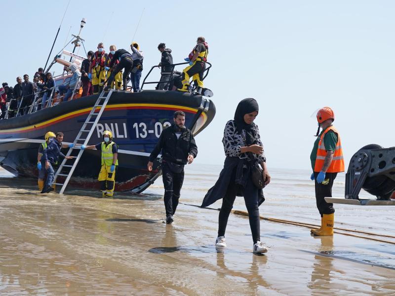 Eine Gruppe von Menschen, bei denen es sich vermutlich um Migranten handelt, geht von Bord des örtlichen Rettungsboots in Kent, nachdem sie nach einem Zwischenfall mit einem kleinen Boot im Ärmelkanal aufgegriffen wurde. Foto: Gareth Fuller/PA Wire/dpa (© Gareth Fuller)