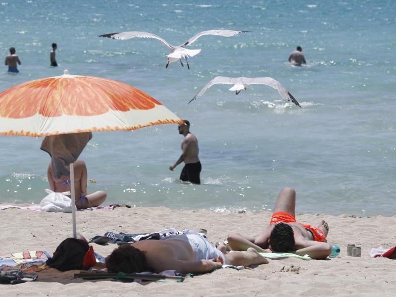 Touristen genießen die Sonne am Strand von Arenal. Foto: Clara Margais/dpa (© Clara Margais)