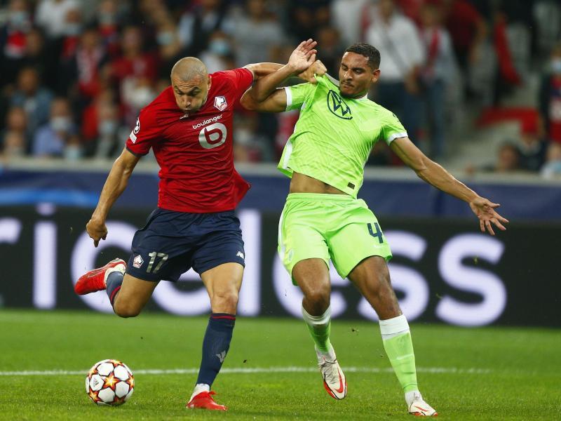 Maxence Lacroix vom VfL Wolfsburg (r) kann sich im Kampf um den Ball nicht gegen Burak Yilmaz vom OSC Lille durchsetzen. Foto: Michel Spingler/AP/dpa (© Michel Spingler)