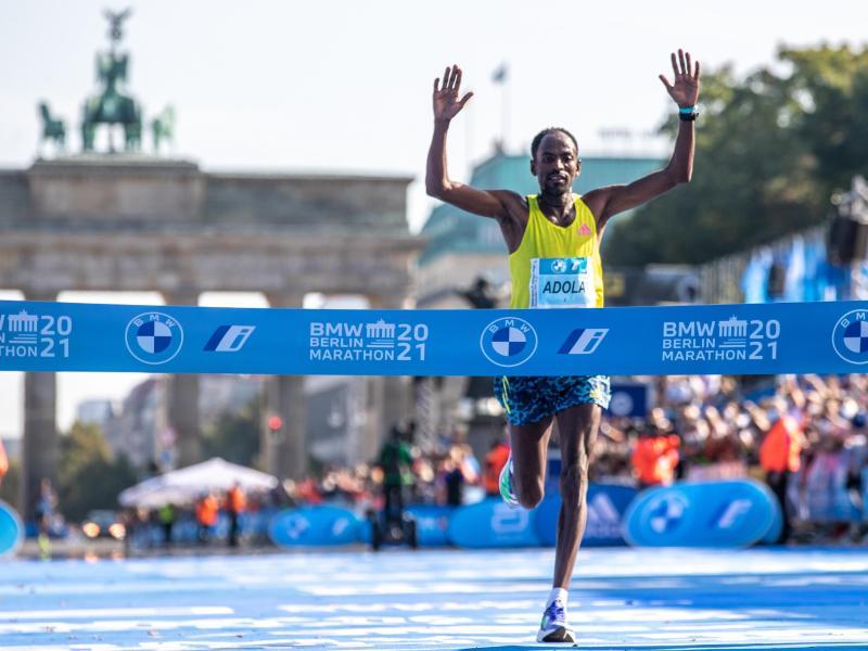 Guye Adola aus Äthiopien läuft beim Berlin Marathon nach 2:05:45 Stunden als Erster durchs Ziel. Foto: Andreas Gora/dpa (© Andreas Gora)
