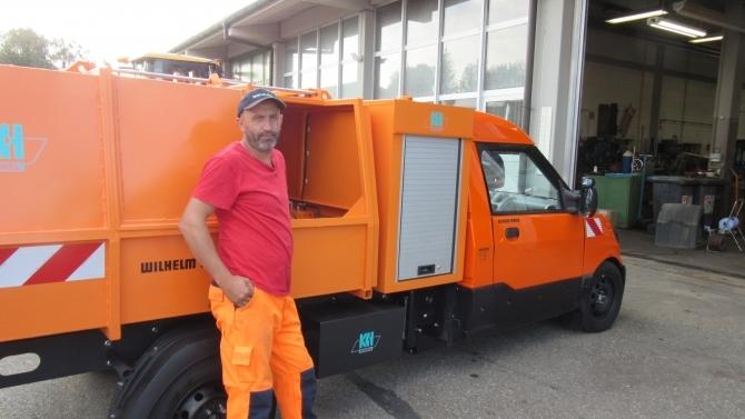 Mitarbeiter Osman Ercin vor dem neuen E-Fahrzeug der Stadt Memmingen (© Tiefbauamt Stadt Memmingen)